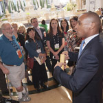 IMEX America attendees listen as Shahid Holmes, assistant director of operations for The Venetian Hotel and Casino, explains how their event staff manages large group arrivals during a